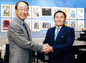 歴代のサッカーW杯公式ポスターを前にがっちりと握手を交わす松井功・日本プロゴルフ協会相談役(左)と、大東和美・Jリーグメディアプロモーション取締役会長
