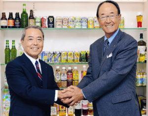 「一番搾り」など人気のキリン製品の前で握手を交わすキリンホールディングス株式会社・三宅占二取締役会長(左)と、松井功・日本プロゴルフ協会相談役(東京・中野のキリンホールディングス本社で)