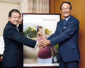 契約している女子プロゴルファー、有村智恵のポスターの前でがっちりと握手を交わす竹中宣雄・ミサワホーム株式会社代表取締役社長(左)と、松井功・日本プロゴルフ協会相談役