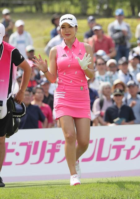 ピンクのミニスカート姿で1番でティーショットを放ち、ファンに手を振るアン・シネ