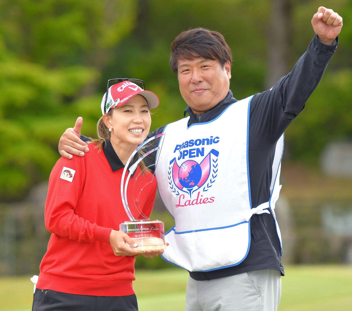 上田はキャディーを務めた辻村明志コーチと優勝トロフィーを手に笑顔
